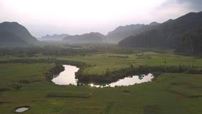 Vasto campo verde vicino al fiume calmo che riflette i raggi gialli del sole stock footage