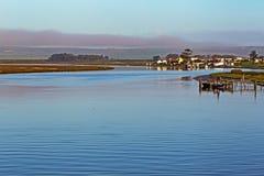Vasto fiume che scorre lentamente oltre moli e case fotografia stock libera da diritti