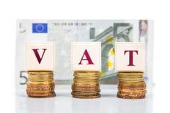 VAT或增值税概念与堆硬币和欧洲货币作为背景 库存图片