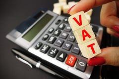 VAT演算概念用举行在木立方体的妇女手大桶词在黑暗的背景的计算器键盘上 免版税图库摄影