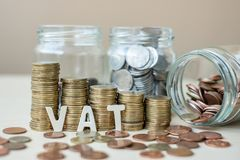 VAT text with golden coin growing money stairs or stack and glass jar on wooden table. business, investment, retirement planning, royalty free stock photo