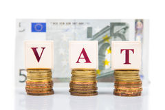 VAT or Value Added Tax concept with stack of coin and EURO currency as backdrop Stock Image
