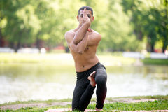 Vatayanasana (horse face pose). Attractive sporty Indian young man working out on riverbank in park, doing Vatayanasana (horse face pose), full length stock images