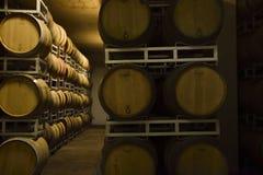 Vaten Italiaanse wijn, merlot en sangiovese, in de kelder stock foto