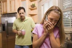 Vater-überwachende Tochter am Telefon Stockfoto