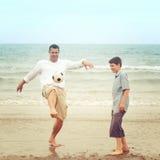 Vater auf dem Strand, der den Ball tritt Stockbild