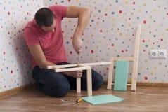 Vater baut einen Stuhl für Kinder zusammen lizenzfreie stockbilder