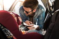 Vater befestigen sein Baby im Autositz stockfotografie