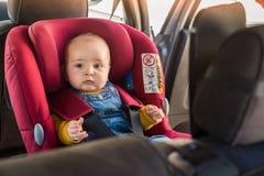 Vater befestigen sein Baby im Autositz stockbilder