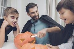 Vater benutzt ein Messer, um einen furchtsamen Kürbis für Halloween zu schnitzen lizenzfreie stockbilder