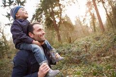Vater-Carrying Son On-Schultern während des Landschafts-Wegs Stockfoto