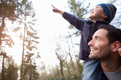 Vater-Carrying Son On-Schultern während des Landschafts-Wegs Lizenzfreie Stockfotos
