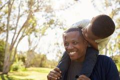 Vater-Carrying Son On-Schultern, wie sie in Park gehen Lizenzfreie Stockfotos