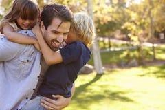 Vater-Carrying Son And-Tochter, wie sie im Park spielen Lizenzfreies Stockfoto