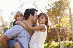 Vater-Carrying Son And-Tochter, wie sie im Park spielen Lizenzfreie Stockfotografie