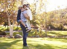 Vater-Carrying Son And-Tochter, wie sie im Park spielen Stockfotografie