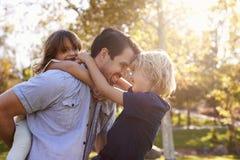 Vater-Carrying Son And-Tochter, wie sie im Park spielen Lizenzfreie Stockfotos