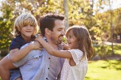 Vater-Carrying Son And-Tochter, wie sie im Park spielen Stockfotos