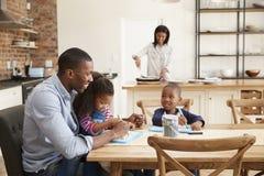 Vater And Children Drawing bei Tisch als Mutter bereitet Mahlzeit vor Stockfotografie