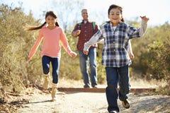 Vater And Children Hiking in der Landschaft Lizenzfreie Stockfotos