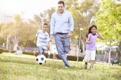 Vater-With Children Playing-Fußball im Park zusammen Stockbilder