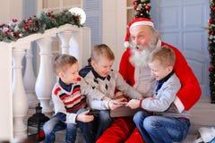 Vater Christmas, das mit frechem Jungen scherzt Stockfotografie