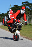 Vater Christmas, das Vorderrad Wheelie tut Stockfoto