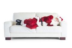 Vater Christmas schläft auf einer Couch lizenzfreie stockfotografie