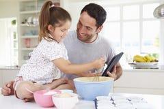 Vater-And Daughter Following-Kuchen-Rezept auf Digital-Tablette Stockfotografie