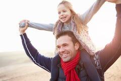 Vater And Daughter Walking auf Winter-Strand lizenzfreie stockfotos