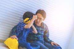 Vater, der auf Kopfhörer für seinen Sohn sich setzt lizenzfreies stockbild
