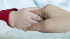 Vater, der Babyhand hält Stockfotografie