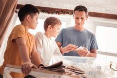 Vater, der das blaue Hemd erkl?rt seinen S?hnen ?ber das Abfallsortieren tr?gt lizenzfreie stockfotografie