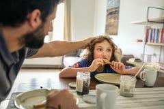 Vater, der das Haar seines jungen Sohns beim Zu Mittag essen zusammen zerzaust lizenzfreies stockfoto