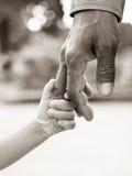 Vater, der dem Kind Hand gibt Stockfoto