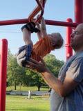 Vater, der den Sohn spielt auf monkeybars unterstützt stockfotografie