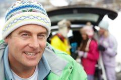 Vater, der an der Kamera lächelt, während Familien-Eingabe Ski fährt Lizenzfreies Stockbild