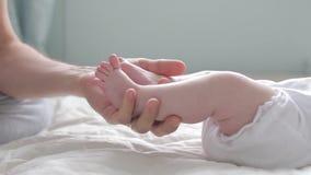 Vater, der die kleinen Zehen seines neugeborenen Babys berührt und zählt Abschluss oben Elternteil, das Neugeborenfüße hält Glück stock video footage