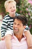 Vater, der draußen Sohn-Fahrt auf Schultern gibt Stockfotos