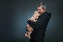 Vater, der ein Baby hält Stockbild