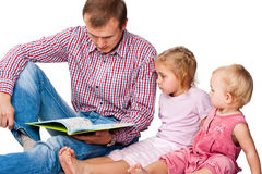 Vater, der ein Buch zu seinen Kindern liest Lizenzfreies Stockfoto