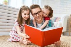 Vater, der ein Buch zu seinen T?chtern liest stockfotos