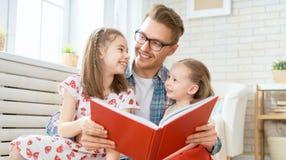 Vater, der ein Buch zu seinen T?chtern liest stockbild