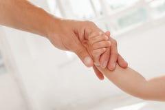 Vater, der einem Kind Hand gibt Stockfoto