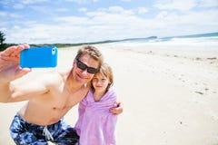 Vater, der Foto mit Tochter am Strand macht Stockbild
