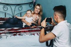 Vater, der Fotos der Mutter und der Tochter macht Stockfoto