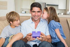 Vater, der Geschenk von liebevollen Kindern empfängt stockbilder