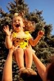 Vater, der herauf das Lachen des kleinen Mädchens anhebt Stockbild