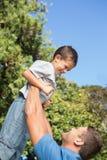 Vater, der herauf seinen Sohn anhebt Lizenzfreies Stockbild
