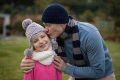Vater, der ihre Tochter im Garten küsst stockfoto
